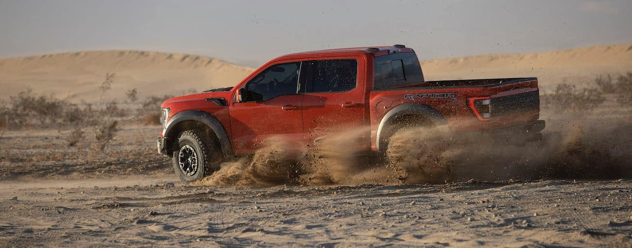 A red 2021 Ford F-150 Raptor is off-roading on dirt.