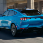A light blue 2021 Ford Mustang Mach-E is driving on an overpass after leaving the Ford SUV dealer in Cincinnati.