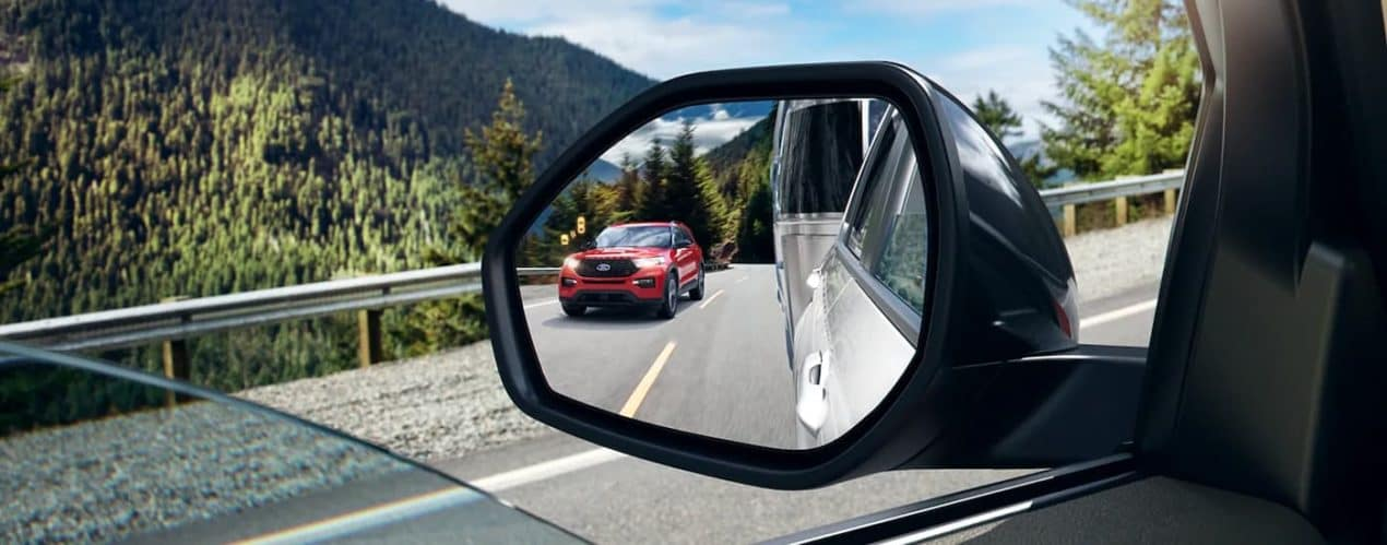 A close up shows the blind spot monitoring icon illuminated on the mirror of a silver 2021 Ford Explorer that is towing a trailer.