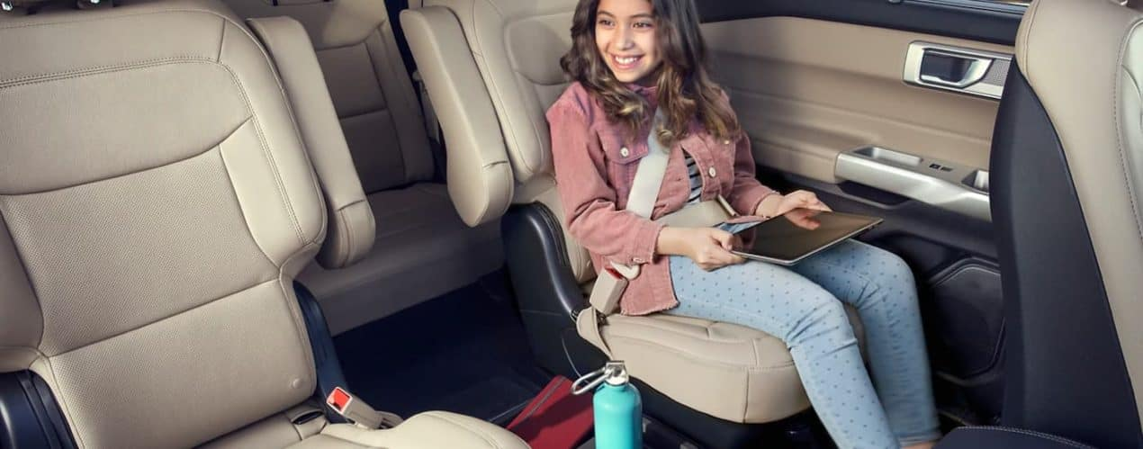A child is shown smiling and using a tabled in the rear seats of a 2021 Ford Explorer.