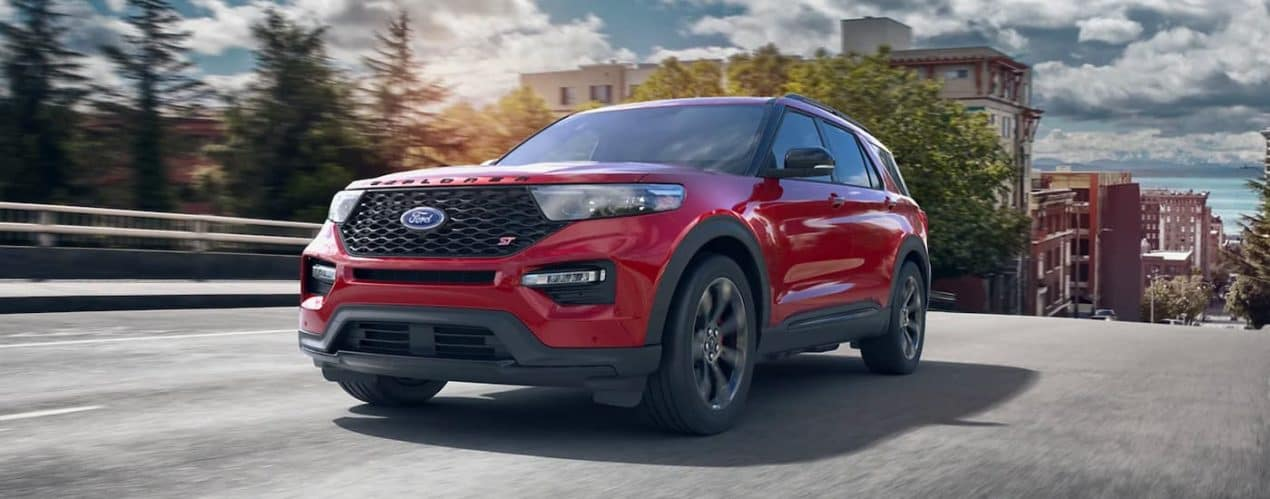 A red 2021 Ford Explorer ST is driving down the road on a sunny day after winning the 2021 Ford Explorer vs 2021 Kia Telluride battle.