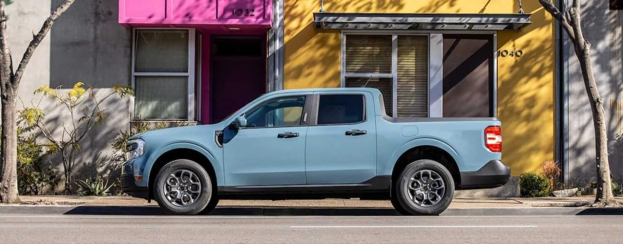 A light blue 2022 Ford Maverick is shown from the side parked in front of a modern store front.