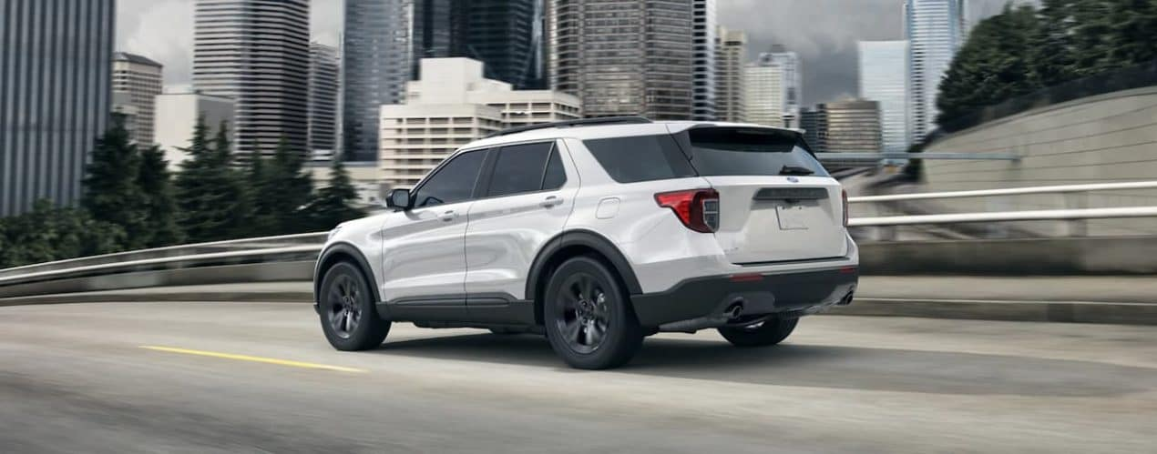 A white 2021 Ford Explorer is driving on a city street after winning the 2021 Ford Explorer vs 2021 Chevy Traverse comparison.