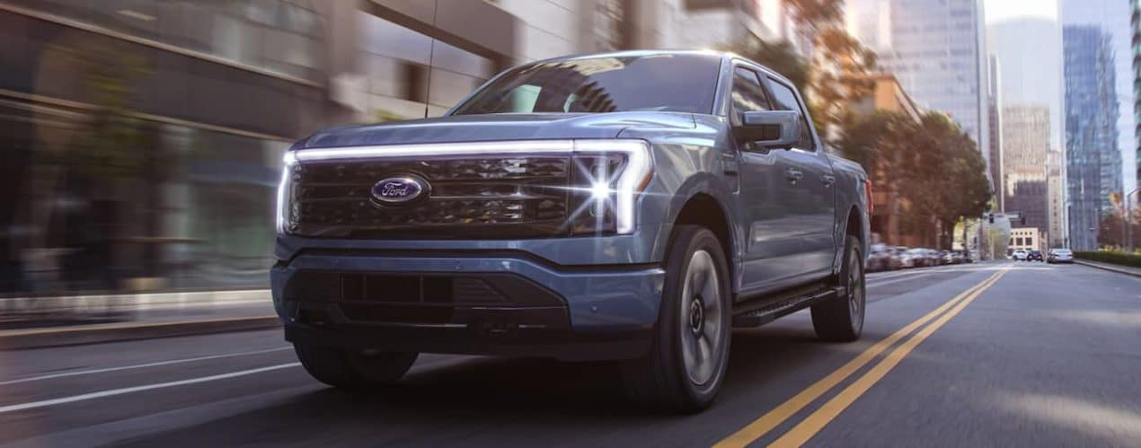 A blue 2022 Ford F-150 Lightning is shown driving through a city.
