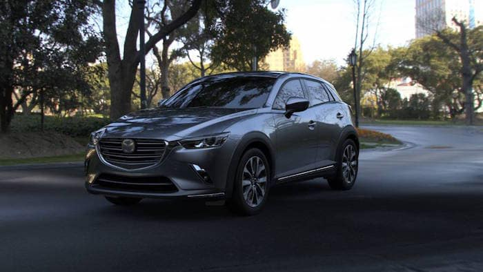 Gray 2019 CX-3 driving near park at dusk