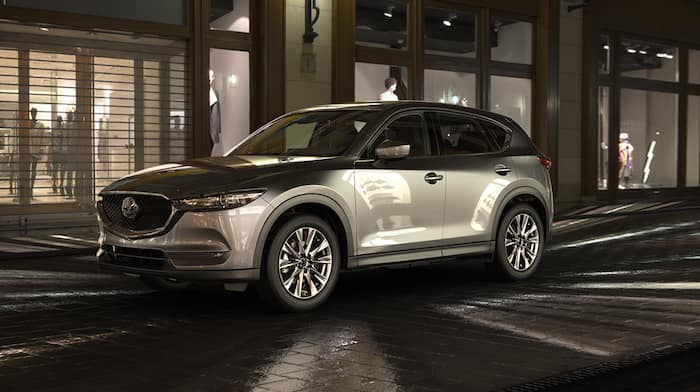 Gray 2019 CX-5 driving near shops at night
