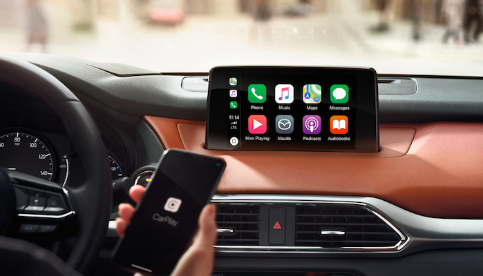 Holding holding iPhone with Apple CarPlay near Mazda CX-9 touchscreen interface