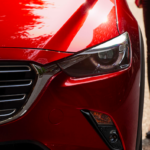 Closeup of Mazda CX-3 front grille with legs of woman standing next car visible to the side