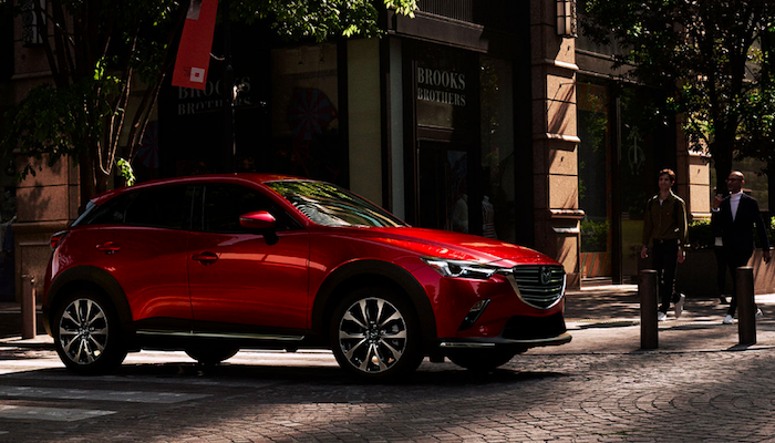 Red Mazda CX-3 in crosswalk with two pedestrians standing off to the right side