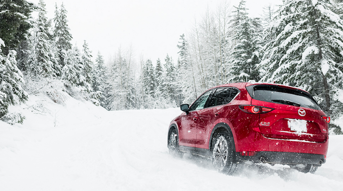Red Mazda CX-5 driving through snow near forest