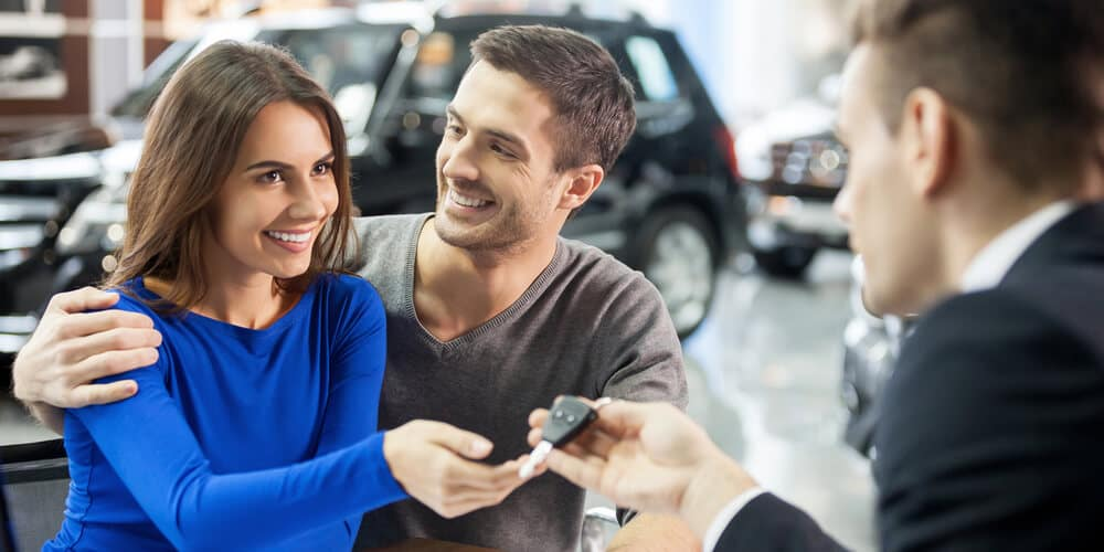 Car salesman giving the key to couple