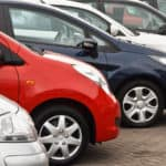 Row of red, white, and blue used vehicles on a car lot