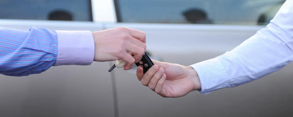 One man hands the keys to the car