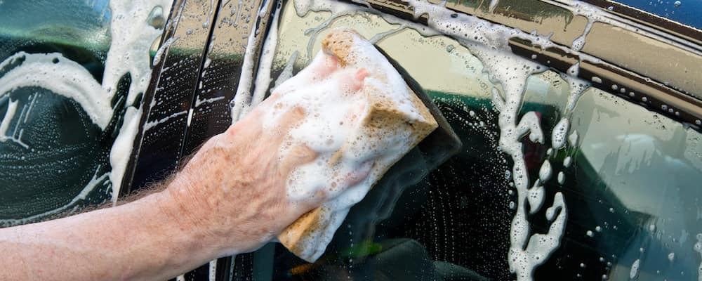 man washing window of car