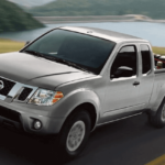 white nissan frontier truck towing car on trailer
