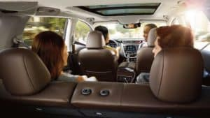 Image of four people sitting inside a 2019 Nissan Murano and chatting.