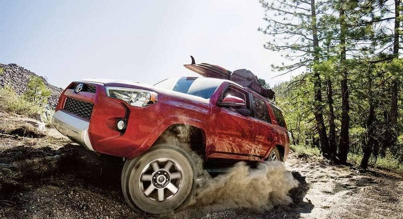 Red 4Runner turning toward camera and kicking up dust