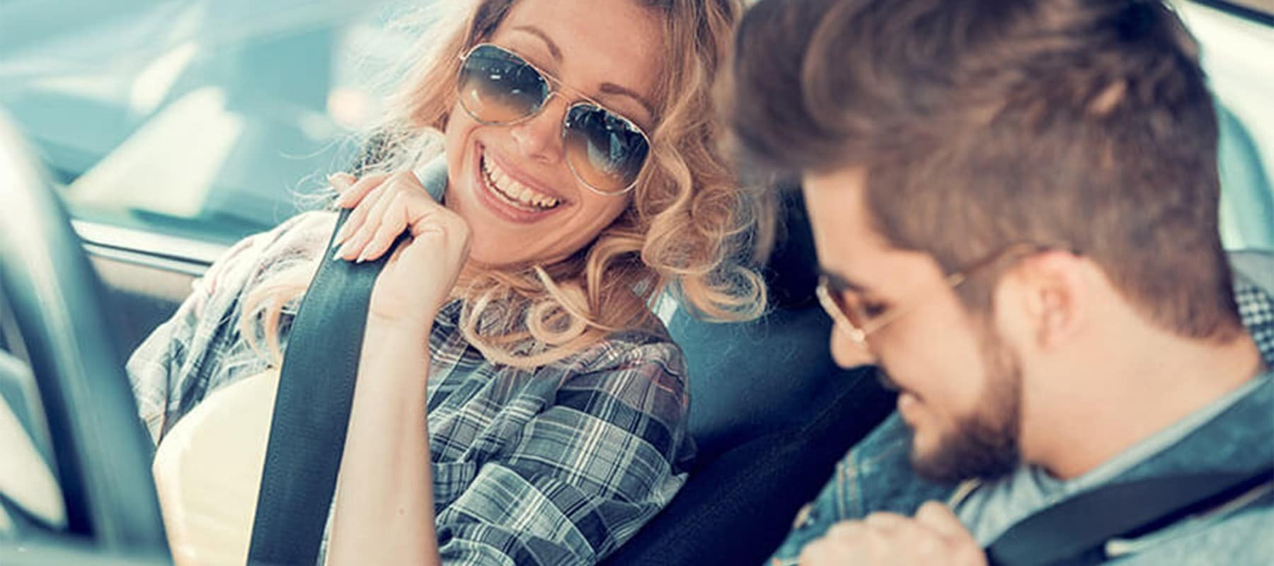 Two-People-Driving-In-Convertible-Smiling