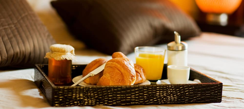 photo of tray with breakfast food on hotel bed inside a hotel room