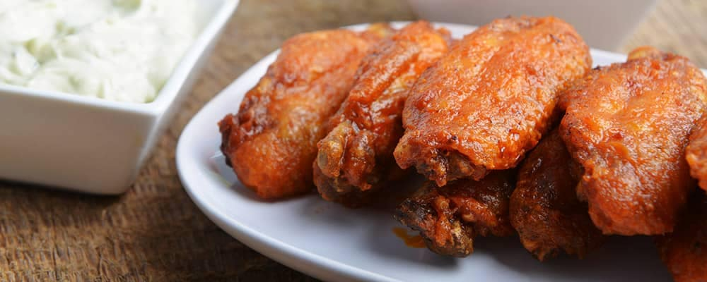 chicken wings on plate with sauce
