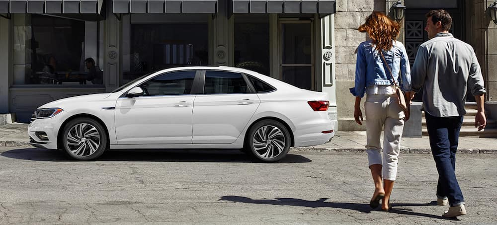 A young couple walking towards their new VW Jetta SEL Premium