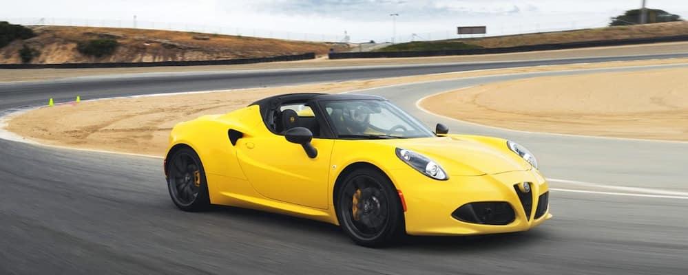 Yellow 2019 Alfa Romeo 4C Coupe driving around a corner