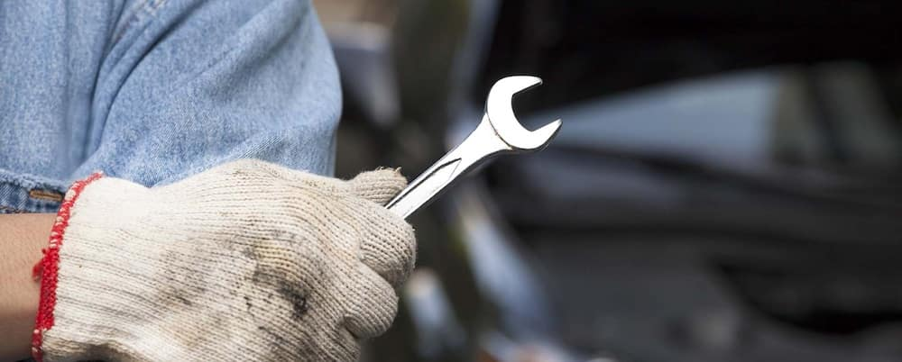 Auto service tech wearing a glove and holding a wrench