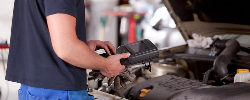 auto mechanic using diagnostic equipment on vehicle
