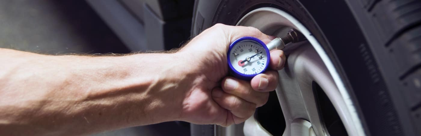 Mechanic checking tire pressure for increased gas milage