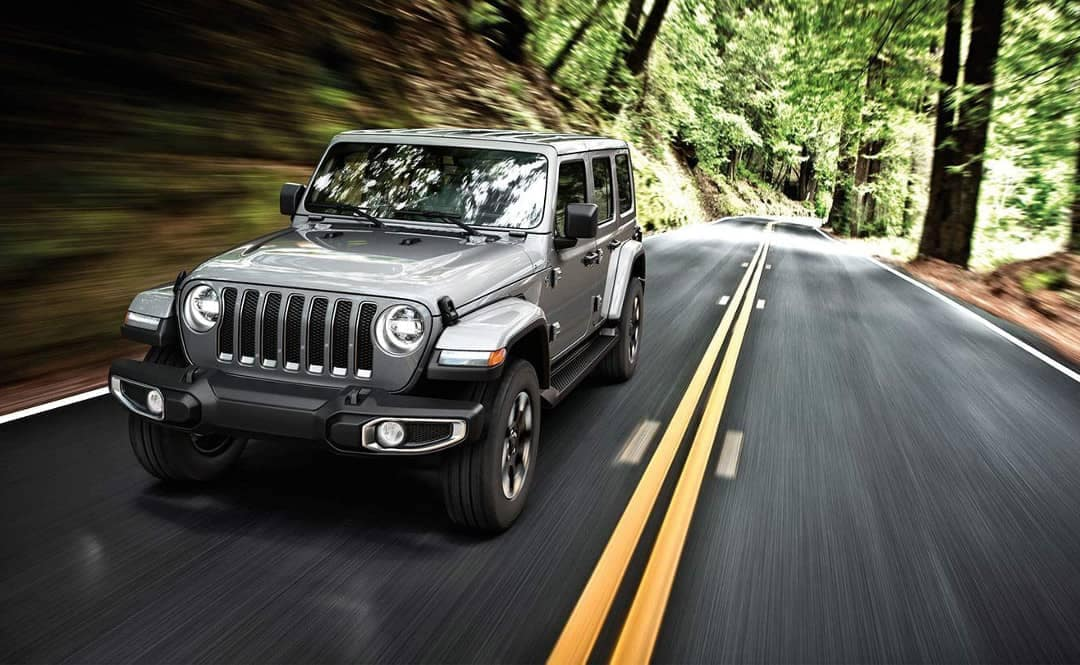 2019 Jeep Wrangler on road through wooded area