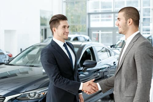 car buyer and salesman shaking hands