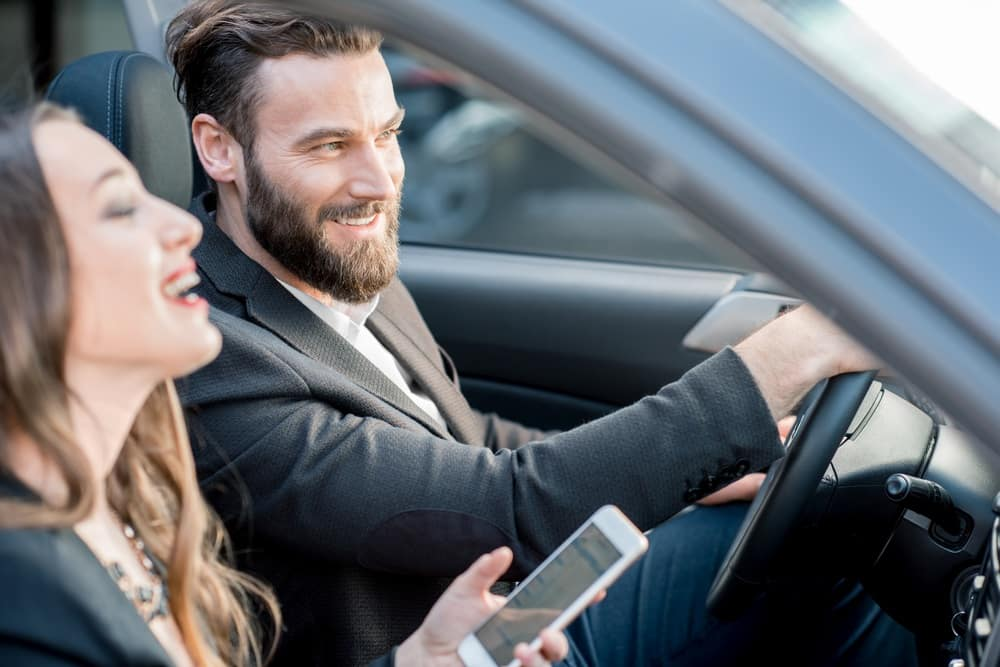 happy new car buyers in front seat of car