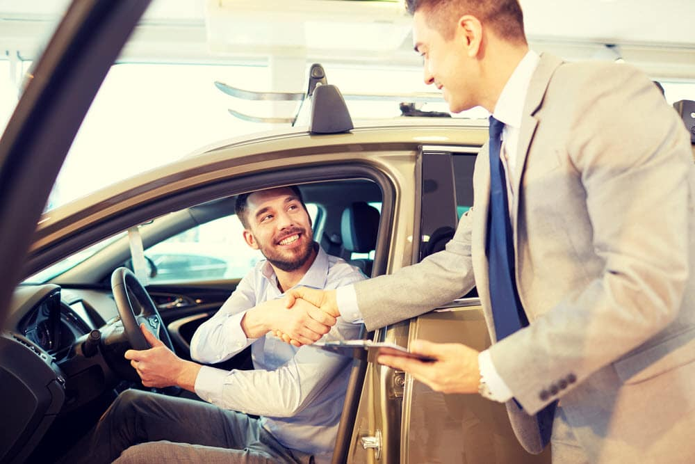 car buyer & salesman shaking hands