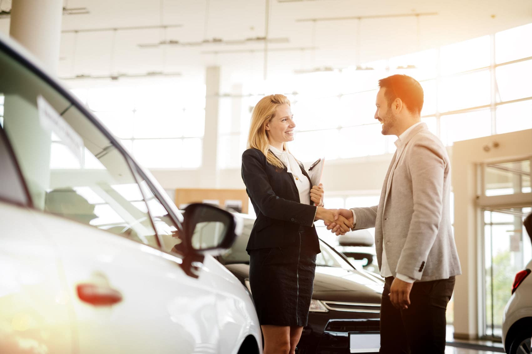 car saleswoman shaking hands with customer