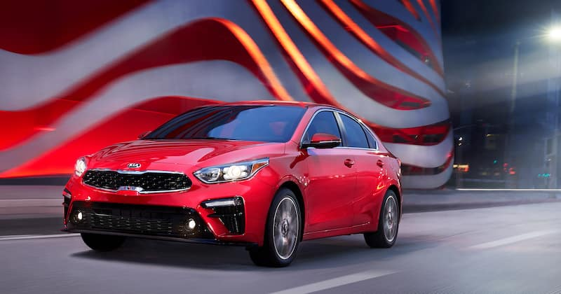 red kia forte driving on the road