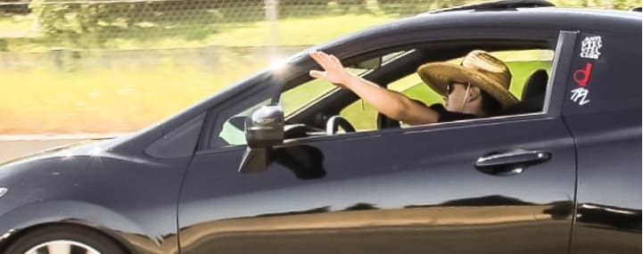 Man waving out of car window